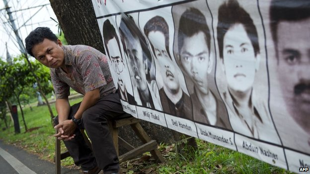 Indonesian torture victim Mugiyanto sits beside a banner showing portraits of missing activists displayed outside the National Commission on Human Rights in Jakarta on 30 May 2014