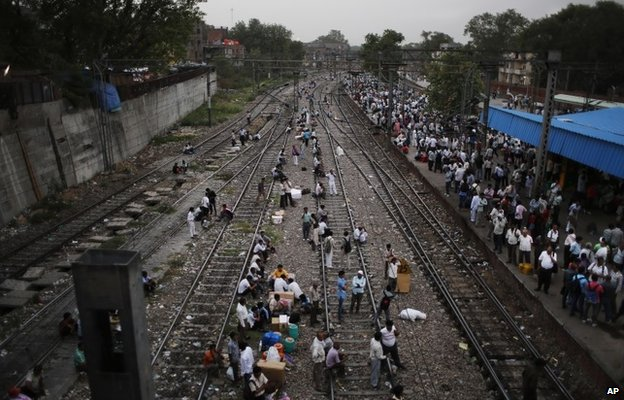 Indian people cross a railway track in Delhi, India.