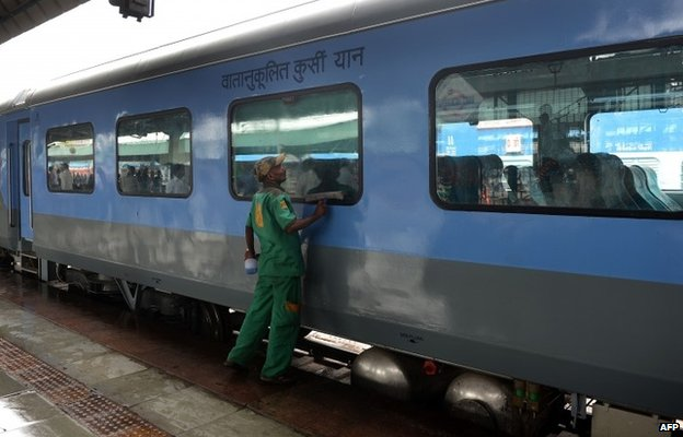 An Indian railways worker cleans a coach prior to the trial run of a high-speed train between New Delhi and Agra