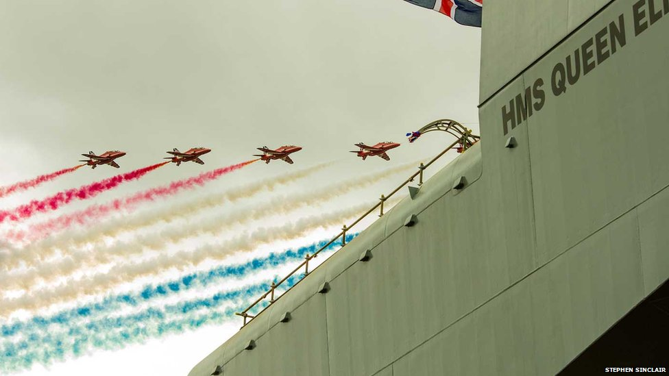The Red Arrow drop red, white and blue vapour trails over The HMS Queen Elizabeth II
