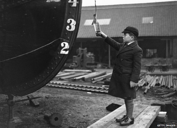 A boy prepares to smash a bottle against his boat