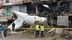 Police officers gather to inspect the scene of a plane crash in a suburb of Nairobi, Kenya