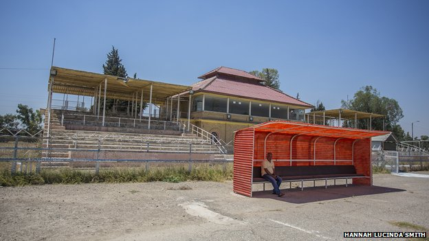 A coach sits in front of an empty stand at Kirkuk FC