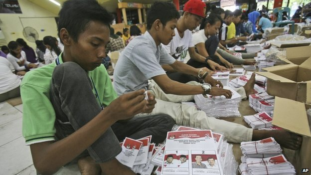Workers fold ballots bearing portraits of Indonesian presidential candidates (L-R) Prabowo Subianto with his running mate Hatta Rajasa and Joko Widodo with his running mate Jusuf Kalla