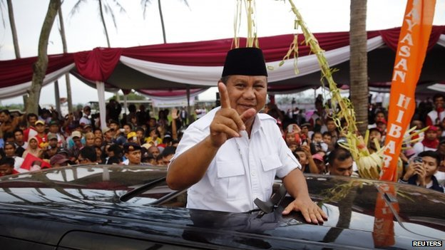 Indonesian presidential candidate Prabowo Subianto gestures as he leaves a campaign rally in Ciparay near Bandung, West Java
