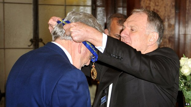 Australia's High Commissioner, John Dauth, presenting Rolf Harris with his medal