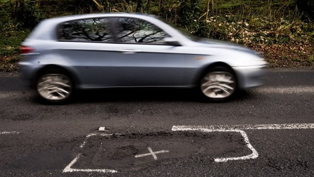 File photo dated 06/01/13 of a car on a potholed road in Gloucestershire