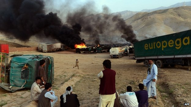 Afghan residents look on as smoke rises from burning fuel trucks following an overnight attack by Taliban militants in Chawk-e-Arghandi on the outskirts of Kabul (5 July 2014)