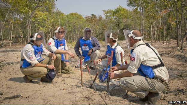 Five men crouching and wearing protective equipment