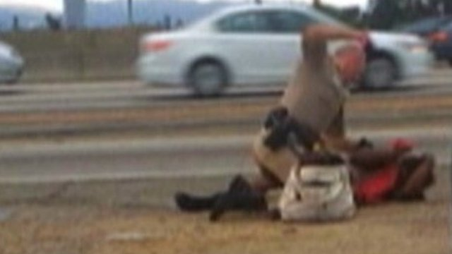 A California Highway Patrol officer straddles the woman on a Los Angeles freeway while punching her in the head