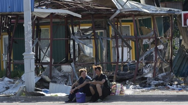 Women sit near a destroyed shop in the city of Sloviansk, July 5