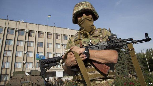Soldier standing in front of government building flying Ukrainian flag in Sloviansk
