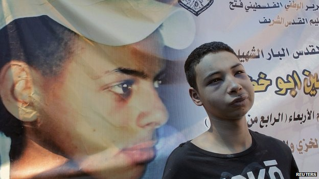 Tariq Khdair stands in front of poster of his murdered cousin, Mohammed Abu Khdair. 6 July 2014