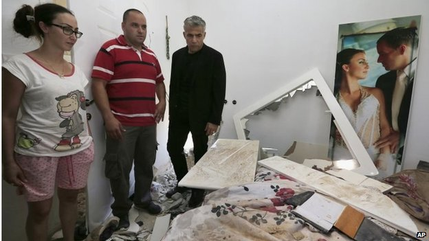 Israeli minister Yair Lapid (right) views rocket damage in a home in Sderot