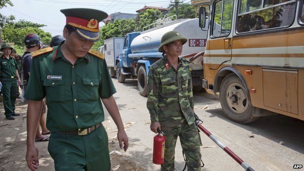 Vietnamese soldiers working at the scene of a helicopter crash walk past backed-up traffic in the Thach That district in the western parts of Hanoi on 7 July, 2014