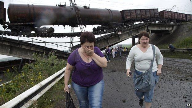 People walk under a destroyed railroad bridge over a main road leading into Donetsk, near the village of Novobakhmutivka, 20km north of Donetsk, eastern Ukraine (7 July 2014)