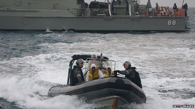 Australian navy personnel transfer asylum-seekers to Indonesian rescue boat near Panaitan island, West Java. 31 August 2012