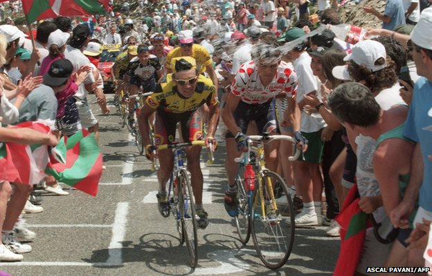 A fan sprays water on Frenchman Richard Virenque, wearing the red and white Polka Dot Jersey of the best climber, during the Port de Larrau Pass climb, 1996