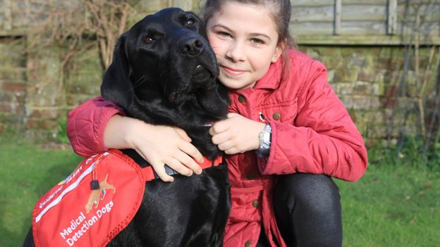 A young girl Gemma hugging Polo, her medical detection dog