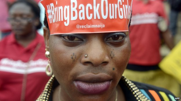 "A woman with a sticker on her head bearing the slogan ""Bring back our girls"" marches for the release of the more than 200 abducted Chibok schoolgirls - Lagos, Nigeria (29 May 2014)"