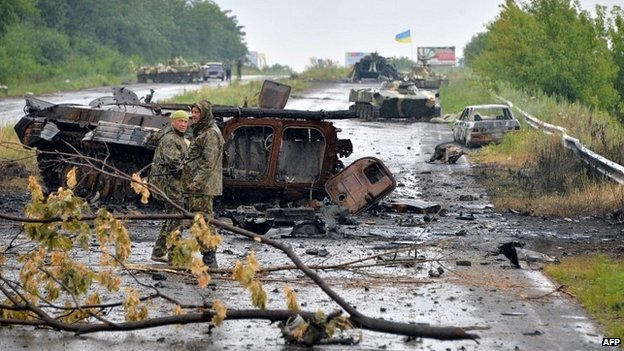 Ukrainian government soldiers stand in front of wrecked tanks and armoured personnel carriers left by pro-Russian insurgents on the outskirts of Sloviansk - 7 July 2014