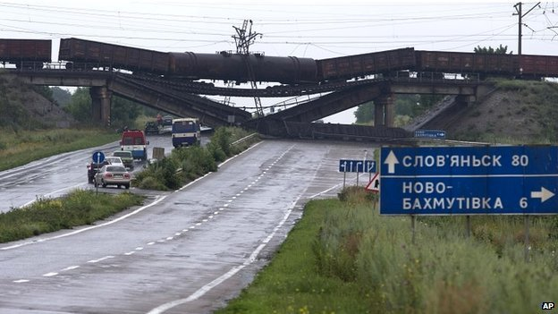 Cars queue to drive under a destroyed railroad bridge near the village of Novobakhmutivka - 7 July 2014
