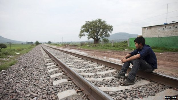 Migrant Santos Tome Hernandes, 16, from Honduras, sits on the railway tracks in Huehuetoca, outskirts of Mexico City 26 June 2014
