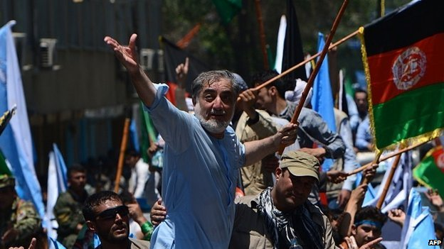 Afghan presidential candidate Abdullah Abdullah (C) throws his hat to supporters during a demonstration in Kabul on June 27, 2014.