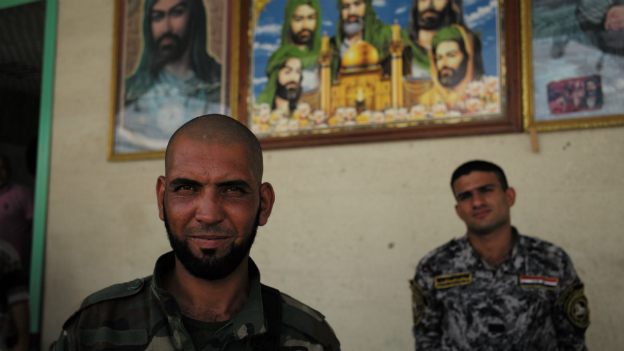 Two members of Asaib Ahl al-Haqq stand outside their headquarters north of Baghdad - July 2014