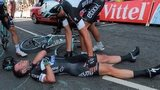 Cavendish lies injured as an Omega Pharma - Quick-Step team-mate looks over him