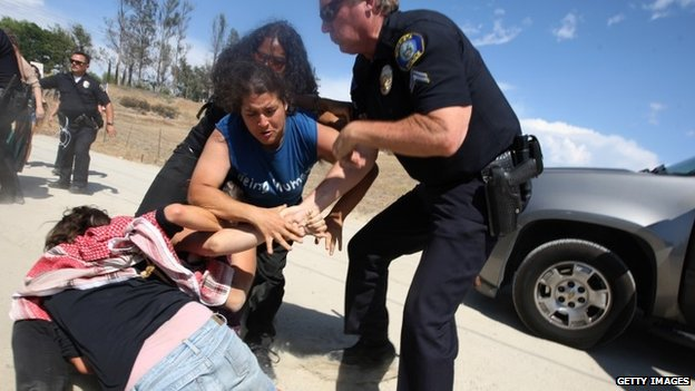 Counter-demonstrators to protesters opposing arrivals of buses carrying largely women and children undocumented migrants for processing at the Murrieta Border Patrol Station clash with police on in Murietta California 4 July 2014