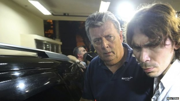 Ray Whelan (left) is escorted to a police station in Rio de Janeiro. Photo: 7 July 2014