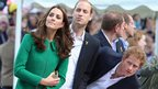 The Duke and Duchess of Cambridge and Prince Harry try to get a glimpse of the riders as they head for the finish line