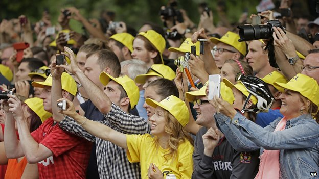 Spectators take pictures of the podium ceremony of the third stage of the Tour de France cycling race