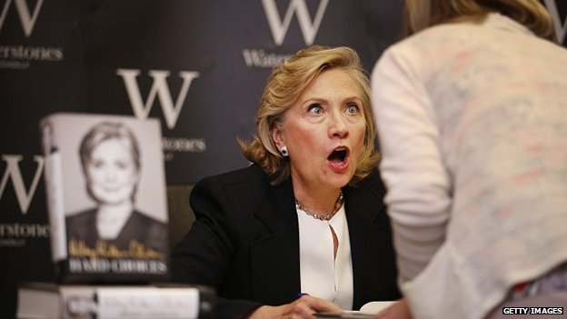 Former US Secretary of State Hillary Clinton looks up at a customer as she signs copies of her new book at Waterstones bookshop on 3 July, 2014 in London