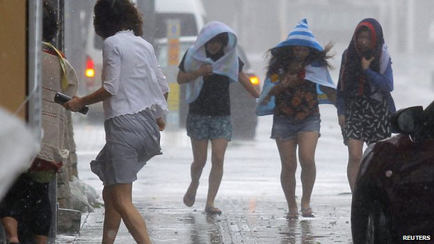 Women walk in strong winds caused by typhoon Neoguri at Kokusai street, a shopping and amusement district in Naha, on Japan's southern island of Okinawa, in this photo taken on 8  July, 2014