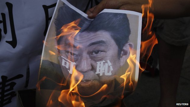 "A protester burns a portrait of Japanese Prime Minister Shinzo Abe, with the Chinese characters ""Shameful"" written on it, outside the Japanese Consulate in Hong Kong on 7 July, 2014"