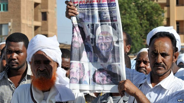 A Sudanese sympathizer holds up a local newspaper showing images of killed Al-Qaeda mastermind Osama Bin Laden as they gather to hold prayers on 3 May 2011, in Khartoum,