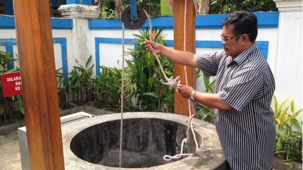 Museum keeper Gatot Nugroho draws water from a well