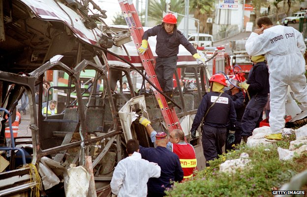 Israeli emergency and security personnel inspect a bus destroyed in a suicide bombing in Haifa on 2 December 2001