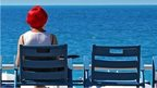 A woman faces the Mediterranean Sea as she sits on the Promenade des Anglais in Nice, France