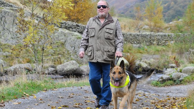 A blind man and his guide dog walking down a rural path in the countryside