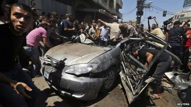 Palestinians gather around a car in Gaza City that medics said was hit by an Israeli missile, killing four people (8 July 2014)