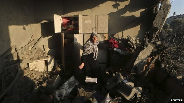 A woman inspects damage to her home in Gaza City after a Israeli air strike on a neighbour's house (8 July 2014)
