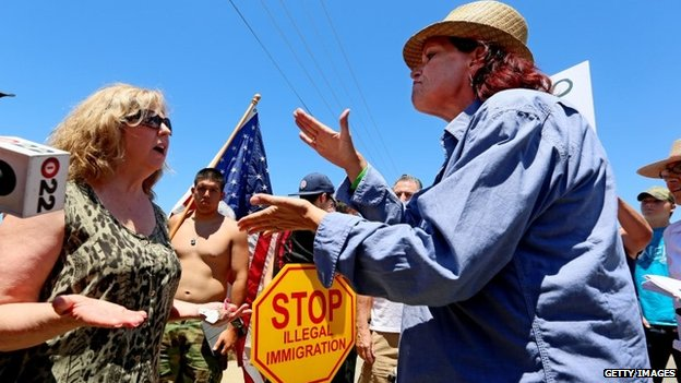 Anti-immigration activist Sabina Durden (R) and immigration sympathizer Mary Estrada (L) debate during a protest outside of the US Border Patrol Murrieta Station 7 July 2014