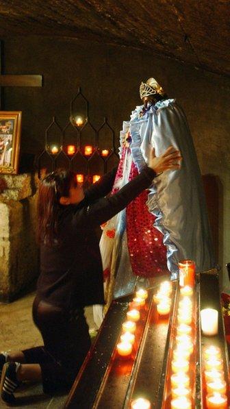 A Gypsy woman prays at the statue of Sara la Kali