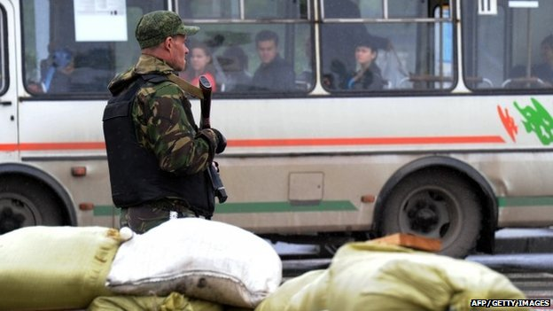 A pro-Russian militant stands guard at a checkpoint on 8 July 2014 in Donetsk