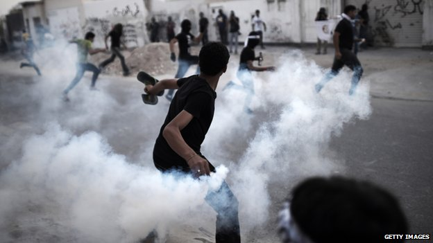 A Bahraini protestor threw a tear gas canister at riot police during clashes in Bahrain on 25 April 2014