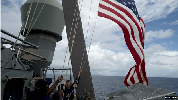 US Navy personnel raise their flag during Cooperation Afloat Readiness and Training (CARAT) Philippines 2014, a US-Philippines military exercise, aboard USS John S. McCain in the South China Sea near waters claimed by China on 28 June 2014.