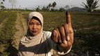 A voter poses for a picture after voting in Indonesia's presidential election in Brambang Darussalam, Bondowoso, East Java on 9 July, 2014